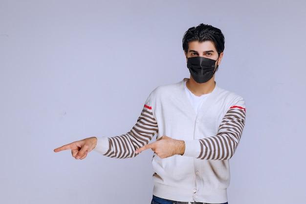 어딘가를 가리키는 검은 마스크를 쓰고 남자.