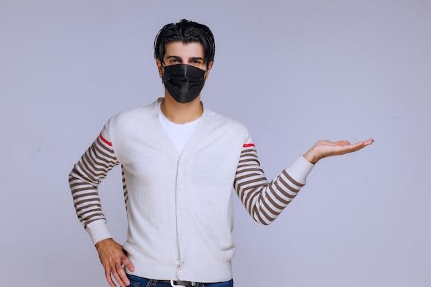 그의 손에 뭔가 제시하는 검은 마스크를 착용하는 남자.