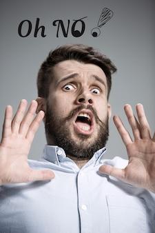 Человек в синей рубашке в испуге говорит о нет над серой стеной