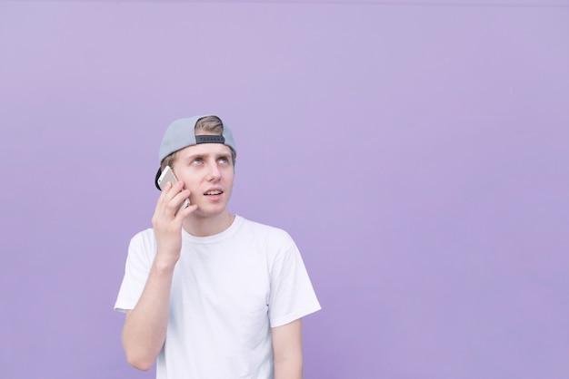Человек в кепке и белой футболке говорит на фиолетовом фоне