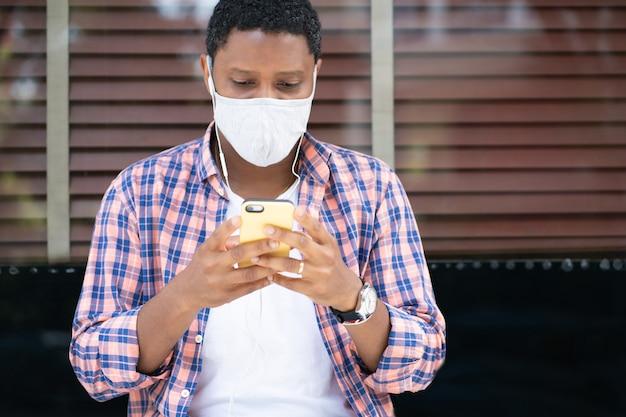 얼굴 마스크를 착용하고 거리의 상점 창에 앉아있는 동안 휴대 전화를 사용하는 남자
