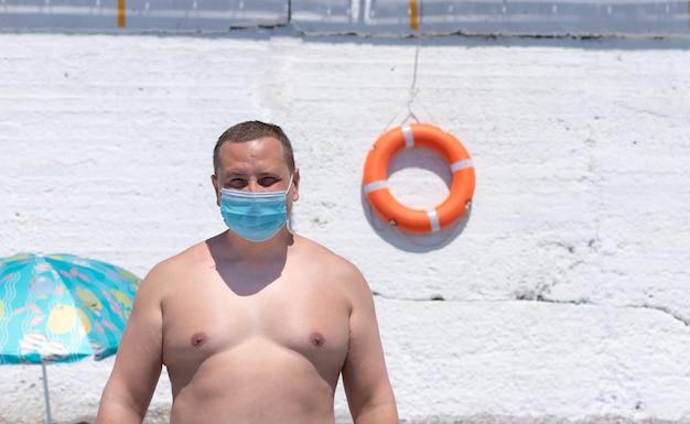ビーチでフェイスマスクを着た男