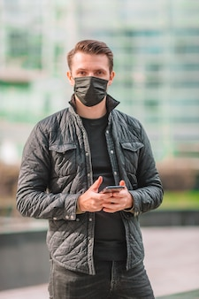 空の街の通りでマスクを着た男。コロナウイルスに対する保護