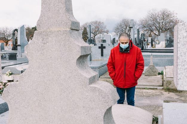 Мужчина в маске, грустный и молящийся, перед могилой умершего родственника во времена covid-19