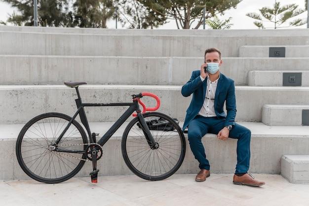 그의 자전거 옆에 앉아있는 동안 의료 마스크를 착용하는 남자