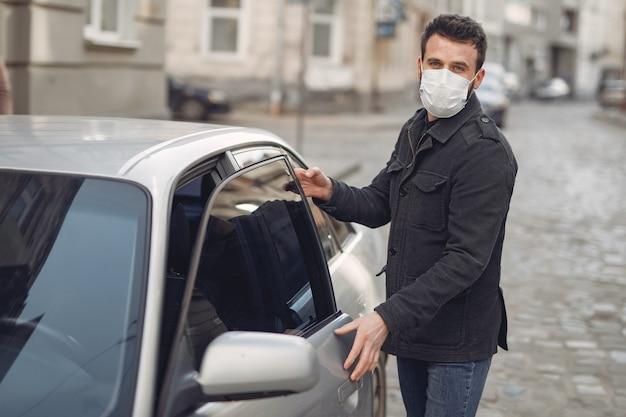 차에 들어가는 보호 마스크를 착용하는 남자