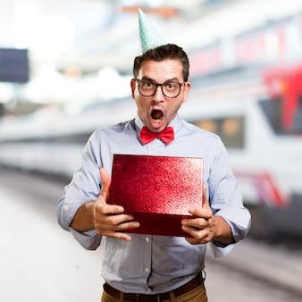Человек, одетый в красный лук галстук и шляпу партии. холдинг подарок. глядя s