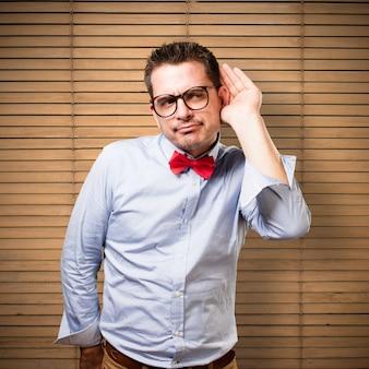 Человек, одетый в красный галстук. обращая внимание на шум.