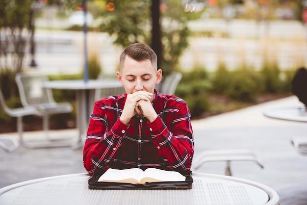 彼の形でnの開いた本を持つテーブルに座っている赤いシャツを着た男