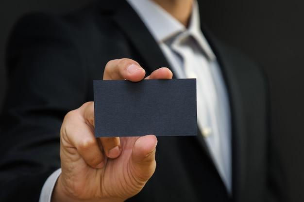검은 벽 표면에 흰색 명함을 들고 양복을 입고 남자.