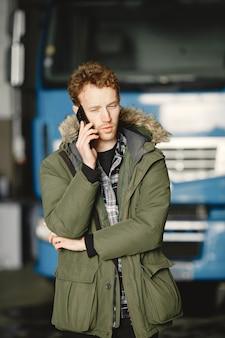 暖かい緑のジャケットを着ている男。ガレージに駐車したトラック。ロジスティクスの問題を解決する
