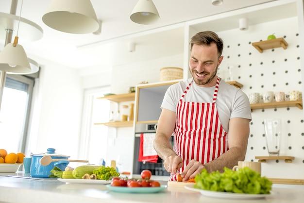 빨간 선이있는 흰색 앞치마를 입고 부엌에서 요리하는 남자