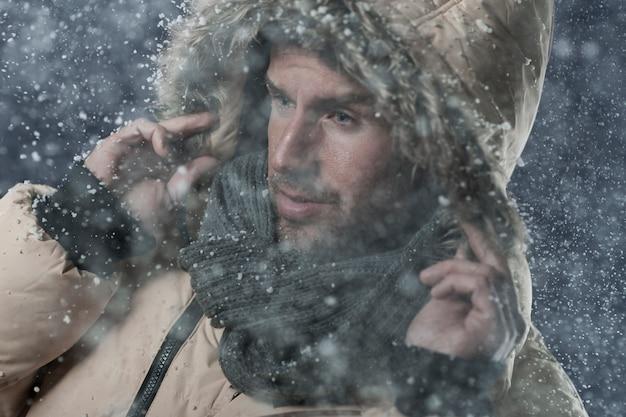 Человек в зимней куртке во время снегопада
