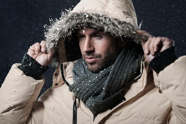 雪が降っている間に冬のジャケットを着ている男