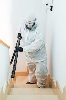 Мужчина в сиз поднимается по лестнице дома, дезинфицирующего от covid-19. концепция здравоохранения пандемии