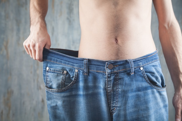 Man wearing big size jeans. weight loss