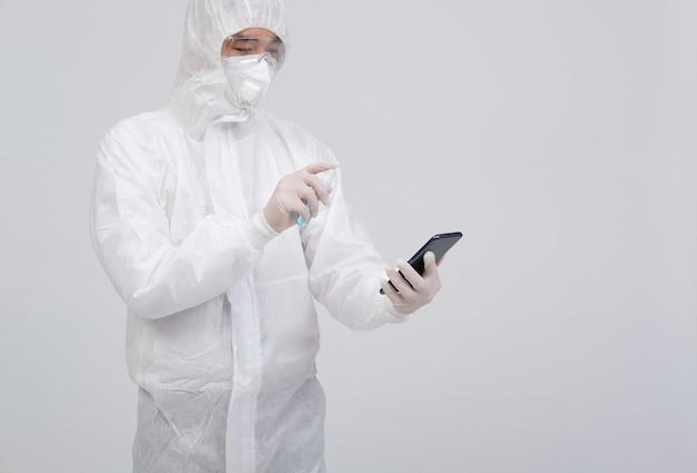 Man wearing biological protective uniform suit clothing, mask, gloves spraying sanitizer on smartphone for sanitizing virus bacteria