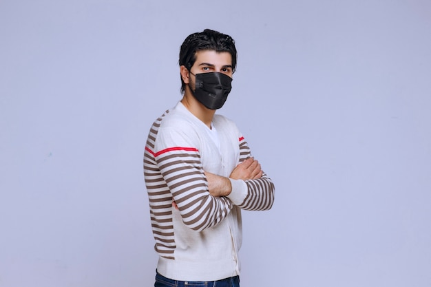 Man wearing a black mask crossing his arms.