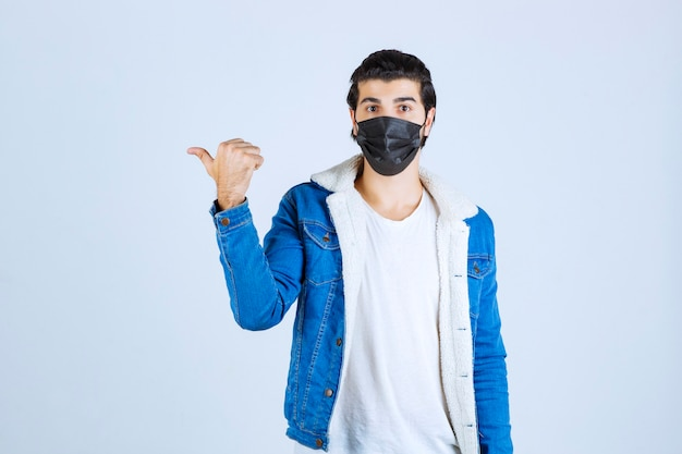 Uomo che indossa una maschera nera e che punta a sinistra.