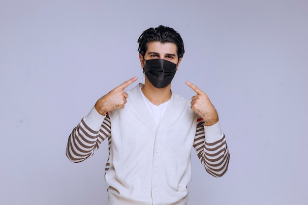 Man wearing a black mask pointing to somewhere.