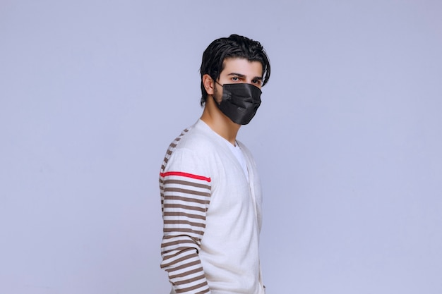 Man wearing a black mask to prevent covid.