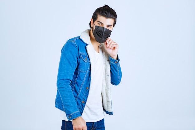 Uomo che indossa una maschera nera e previene il virus corona.