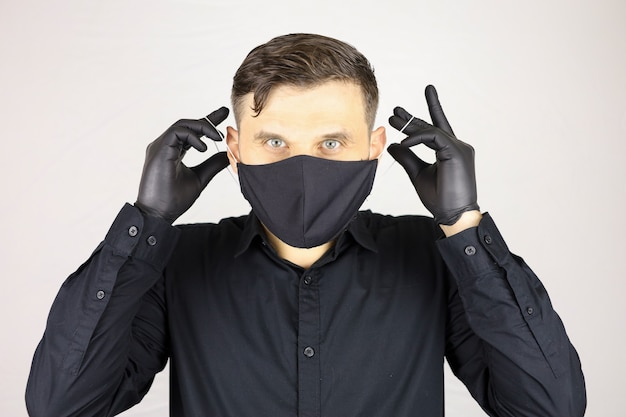 A man wearing black medical gloves removes a protective mask on a white background