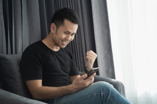 Человек в черной рубашке смотрит на мобильный телефон и счастлив