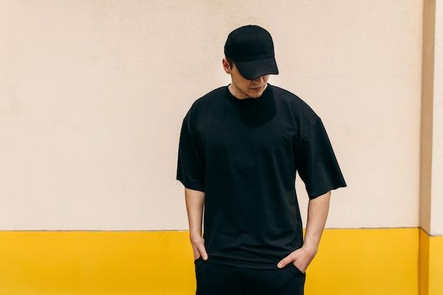 屋外の壁の背景に黒のtシャツと黒の野球帽を身に着けている男