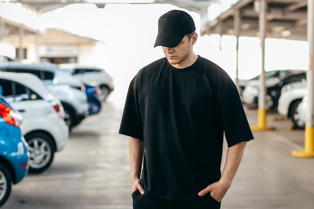 Man wearing black tshirt and a black baseball cap with on a parking background
