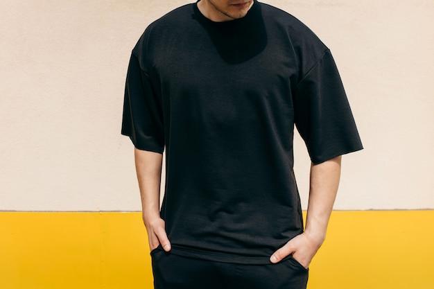 屋外の壁の背景に黒のtシャツを着ている男