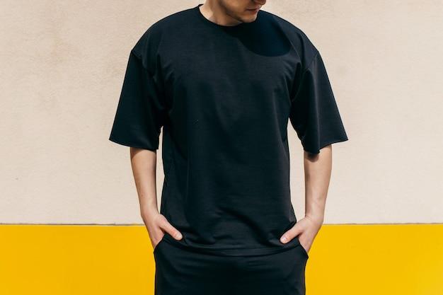야외 벽 바탕에 검은 티셔츠를 입고 남자