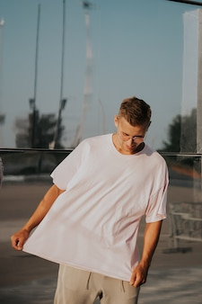 Man wearing blank t-shirt posing against glass mirror wall in the city street, front tshirt mockup on model, urban style