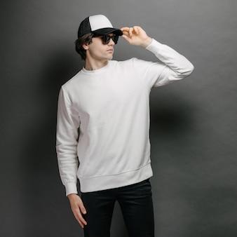 灰色の背景の上に立っている空白の白いスウェットシャツと空の野球帽を身に着けている男。モックアップ、ロゴデザイン、または空きスペースのあるデザインプリント用のスウェットシャツまたはパーカー。