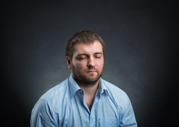 黒の上に目を閉じて夢を見ている青いシャツを着た男