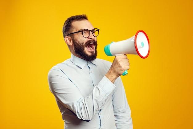 Man wearing blue shirt and eyeglasses standing and screaming in loudspeaker