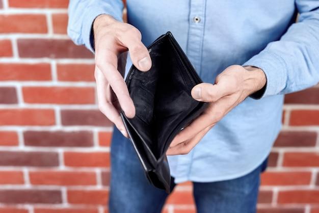 空の黒い財布を示す青いシャツを着た男
