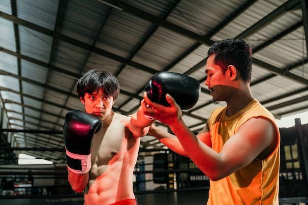 권투 반지에 타격 운동을 하 고 그녀의 트레이너와 함께 권투 장갑을 착용하는 남자. 코치와 함께 남자 복서 훈련