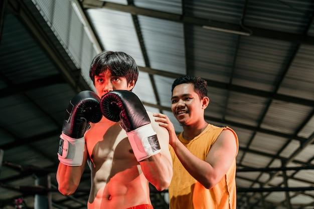 권투 링에 서있는 그녀의 트레이너와 함께 권투 장갑을 끼고 남자. 싸움 휴식 중에 함께 서있는 남자 복서와 트레이너