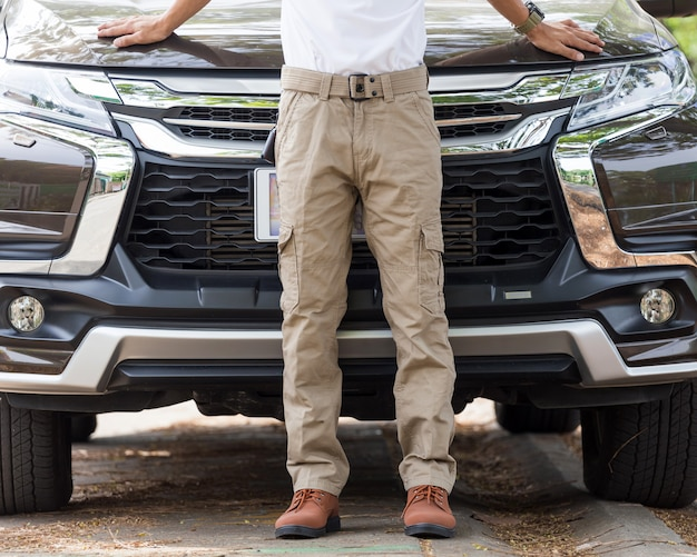 Man wearing cargo pants with suv car parking in the nature park