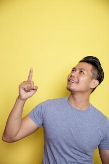 空白を示すカジュアルなtシャツを着ている男性。黄色の壁に分離された思考のアイデア