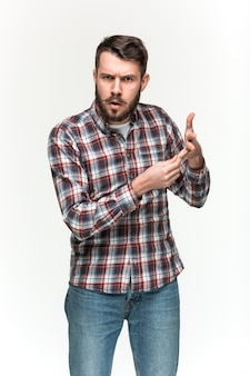 Man wearing a checkered shirt is looking pouter with an imaginary object in his hands. over white space