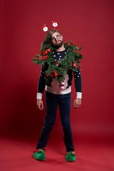 Uomo che indossa abiti natalizi e una ghirlanda
