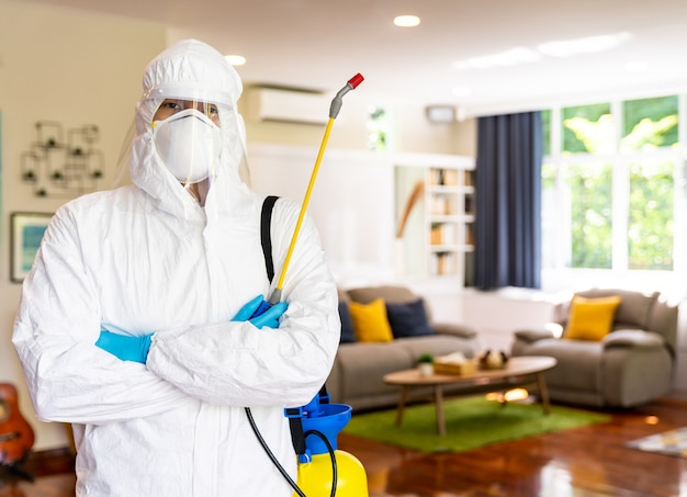 家を掃除するための消毒装置付きのクリーニングスーツを着た男