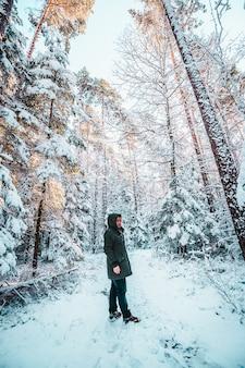 冬の雪に覆われた松林の上を歩くコートとブーツを着た男