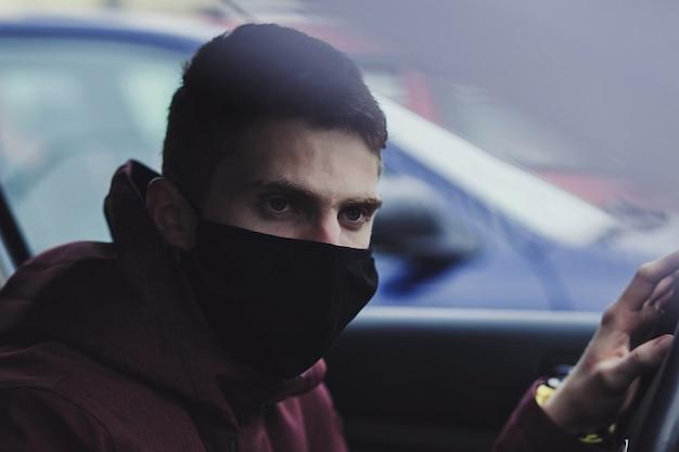 車の使い捨て医療フェイスマスクを着た男