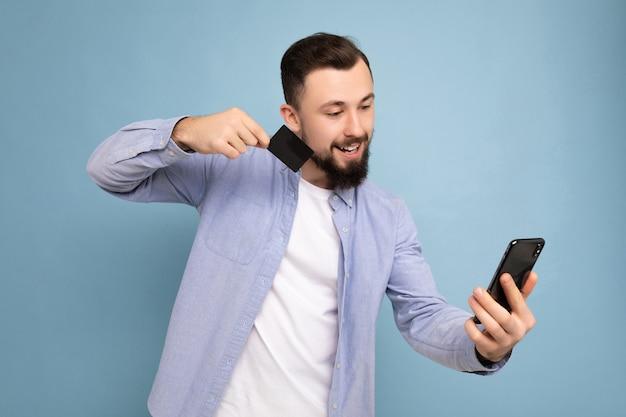 Человек в повседневной одежде изолирован на стене, держа и используя телефон и кредитную карту, делая оплату, глядя на экран смартфона