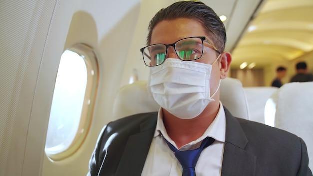 飛行機の中でフェイスマスクを着用している男