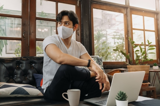 Man wearing face mask is working with laptop in a cafe