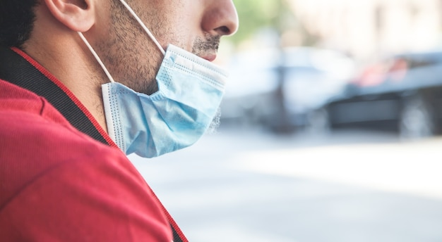 街の通りでフェイスマスクを身に着けている男。コロナウイルス病気
